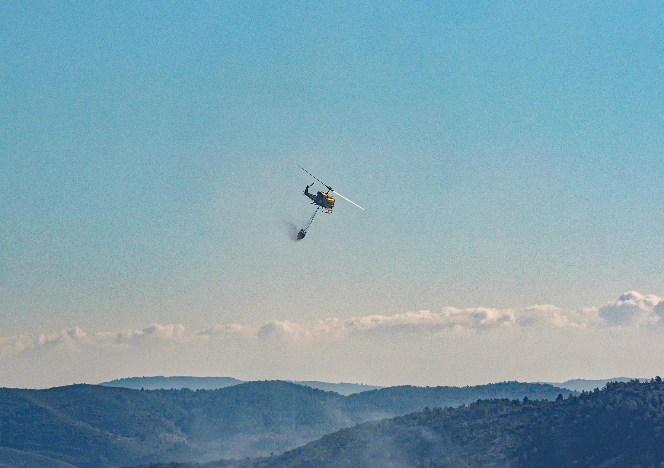 A helicopter carrying water to fight a fire in Spain-3